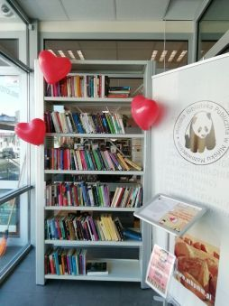 Zdjęcie przedstawiające ozdobioną balonowymi sercami półkę z książkami, które można adoptować