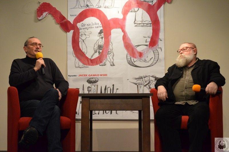 Spotkanie Ogórek i Bralczyk siedzą przy stoliku z mikrofonami w tle okładka ksiazki