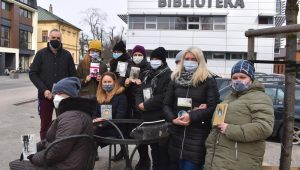 Bibliotekarze przy zniszczonej ławeczce Jana Himilsbacha w Mińsku Mazowieckim trzymają książki napisane przez Himilsbacha w rękach