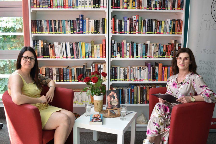 w tle regaly z książkami dwie kobiety w letnich sukienkach i książki