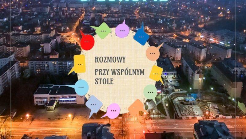 w tle miasto Mińsk Mazowiecki na środku kółko z napisem rozmowy przy wspólnym stole nocą